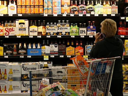 A customer looks over the beer selection in this file photo from Monday, Oct. 1, 2018. Utah Gov. Gary Herbert signed a new state law Tuesday that allows grocery stores to sell beer with up to 4 percent alcohol by weight.