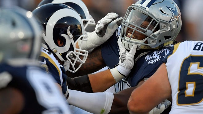 Dallas Cowboys defensive end Taco Charlton, right, gets a hand to the mask from the Los Angeles Rams offensive guard Cody Wichmann during the first half of a preseason NFL football game Saturday, Aug. 12, 2017, in Los Angeles. (AP Photo/Mark J. Terrill)