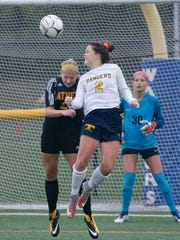 Spencerport's Erin Coykendall reaches for the ball as Greece Athena's Shelby Mancuso defends in the second half during the Class A girls soccer final at Webster Schroeder High School.