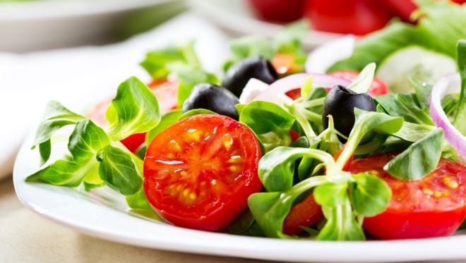 A fresh salad with olives and tomatoes.