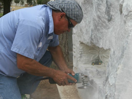 Sculptor Dave Sadler was adding a carved bible on the