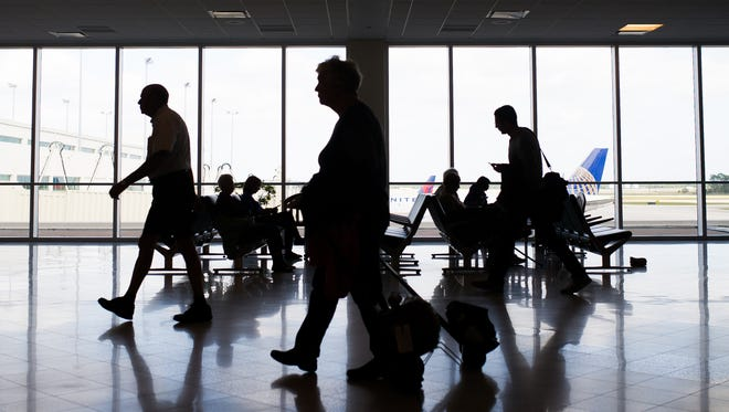 Travelers walk through the terminal at Southwest Florida International Airport in Fort Myers on Saturday, January 23, 2016.