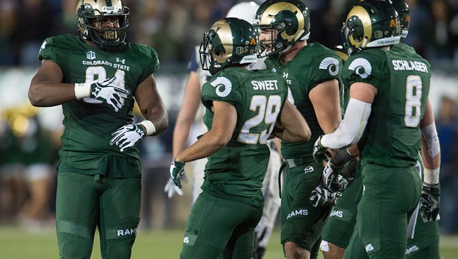 Darnell Thompson, left, and Justin Sweet (29), Jake Schlager (8) and other CSU defenders celebrate one of their four sacks of Utah State quarterback Kent Myers during last Saturday night's game at Hughes Stadium.