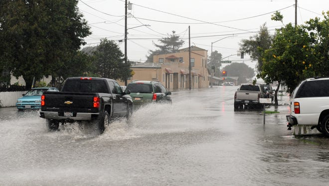 Cars negotiate flooded areas early Sunday morning at the intersection of E. Bolivar St. and Perez St. in north Salinas.