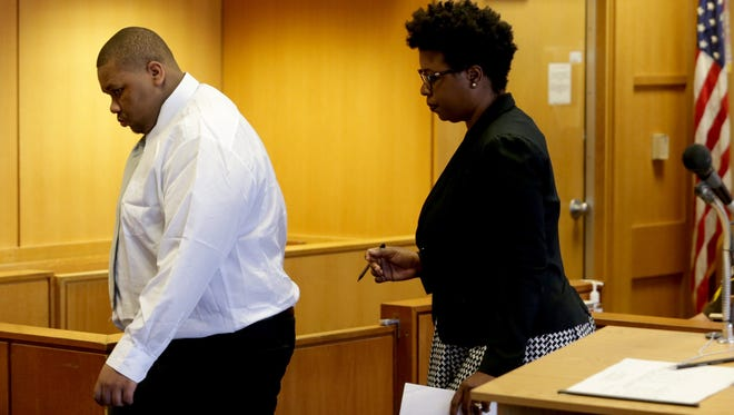 (L to R) Juwan Plummer, 19 walks in front of his lawyer Victoria Burton-Harris looking down and heading out of the courtroom of Judge Kenneth King at the Frank Murphy Hall of Justice in Detroit, Michigan on Wednesday, April 26, 2017.