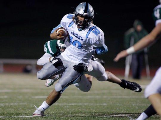 Lansing Catholic quarterback Michael Lynn III (10) breaks a tackle attempt by Olivet's Nick Jungel Friday, Oct. 27, 2017, in Olivet, Mich. Lansing Catholic won 42-20.