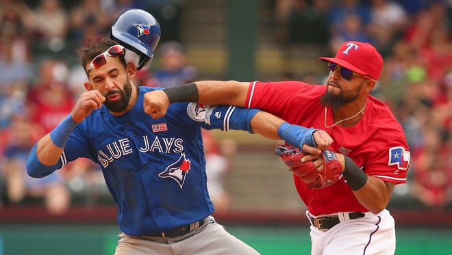 Toronto Blue Jays Jose Bautista (19) gets hit by Texas Rangers second baseman Rougned Odor (12) after Bautista slid into second in the eighth inning of a baseball game at Globe Life Park in Arlington, Texas, Sunday May 15, 2016.