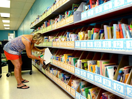 Sally Spedoske, literacy teacher at Sheridan Road Elementary School, works on preparing a section of the library at the school during preparations for the new school year.