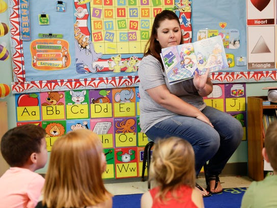 Chelsea LeBlanc reads a story Friday to children at