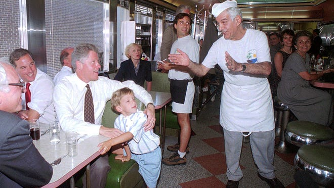 With his arm around Nicholas Lines, President Bill Clinton orders his lunch from Nicholas' grandfather Stratty Lines, right, owner of the Oasis Diner on Monday July 31, 1995. Clinton is seated with Vermont Gov. Howard Dean, seated next to Clinton, and Rep. Bernie Sanders, I-Vt.
