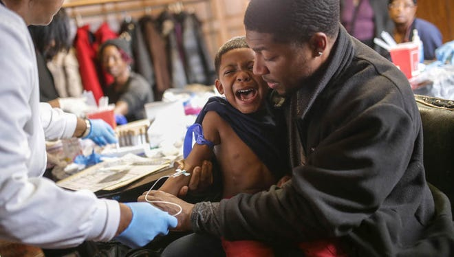 """Mike Henry Sr. of Grand Blanc holds his grandson Kaiden Olivares, 3, as he screams while giving a blood sample to be tested for lead. """"I'm upset I had to do that to him,"""" Henry Sr. said who moved with his family outside of the city to Grand Blanc."""