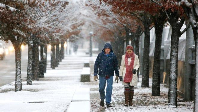Mike and Linda Barnett of Mobile, Ala., walk along Third Street Monday morning.
