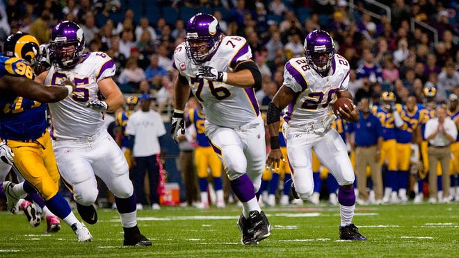 Adrian Peterson of the Minnesota Vikings runs to his left toward the end zone as Steve Hutchinson (76) and John Sullivan (65) lead the way against the Rams on Oct. 11, 2009 in St. Louis, Missouri. (Photo by Dilip Vishwanat/Getty Images)
