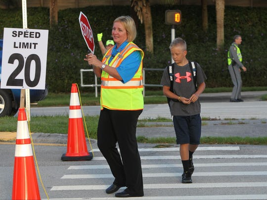 Collier County Schools Superintendent Kamela Patton help students cross the street safely as they arrive at Pelican Marsh Elementary School in Naples Monday, August 17, the first day of classes for Collier County schools.