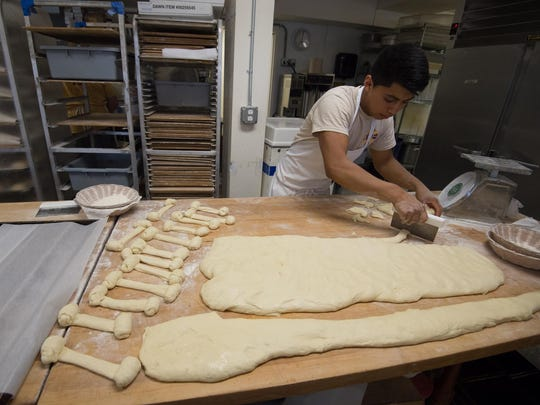 Wilson Ramirez, a baker at Old World Breads in Lewes, cuts dough into smaller sizes to make cinnamon shortys.