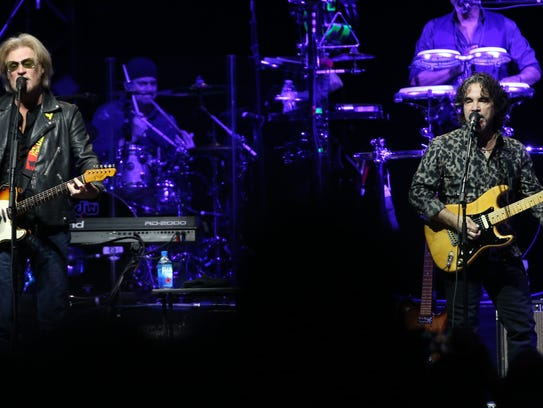 Daryl Hall plays with John Oates (R) in concert at