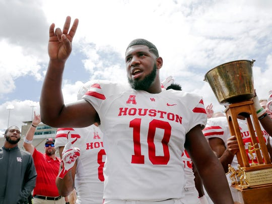 Houston Cougars defensive tackle Ed Oliver does the Cougar Paw with his teammates and the Bayou Bucket trophy after defeating Rice in a NCAA college football game Saturday, Sept. 1, 2018, in Houston.