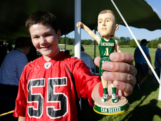 Sam Wallace, 12, of Plymouth smiles as he holds his signed Sam Dekker bobble head doll during Sam Dekker Day Friday July 28, 2017 in Sheboygan, Wis. Dekker, who now plays with the L.A. Clippers had his Lutheran High jersey retired at the event.