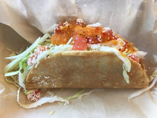 A hard-shell taco filled with soft potato, cabbage