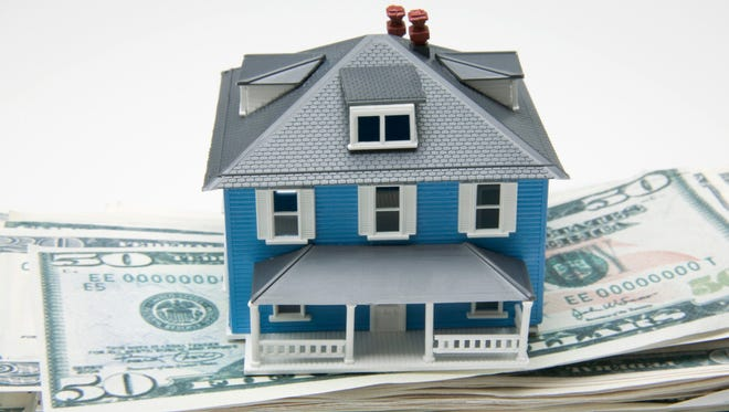 House on stack of money is a stock photo.