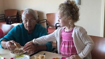 Arden Burns, 3, of Covington, helps Madonna Manor resident Colette Sharp with snack time.