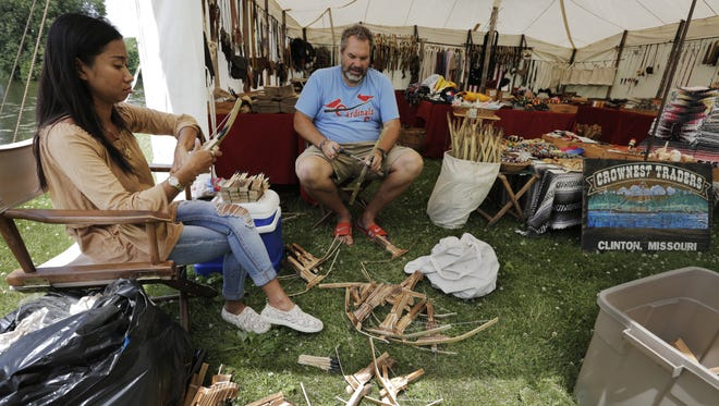 Nok Crowson and Tom Crowson of Crownest Traders, of Clinton, MO assemble bow guns in the historic village area of Sawdust Days at Menominee Park on Wednesday. Sawdust Days begins Thursday and runs through the Fourth of July.