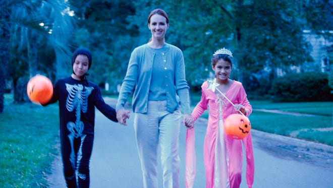 Mother with her son and daughter in Halloween costumes.