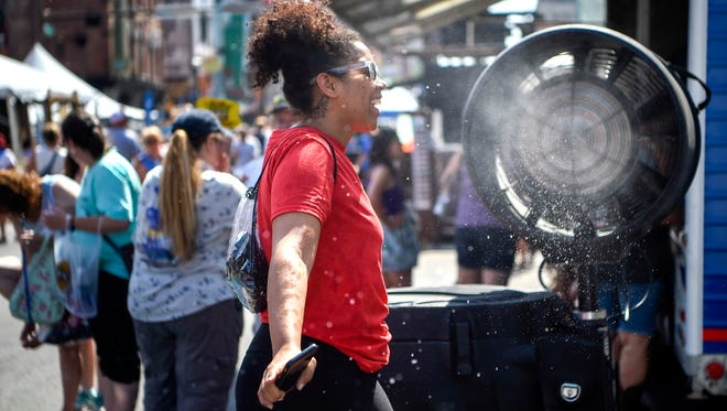 Darci Hayes cools off with a misting fan along Broadway during the CMA Fest week in Nashville, Tenn., Thursday, June 7, 2018.