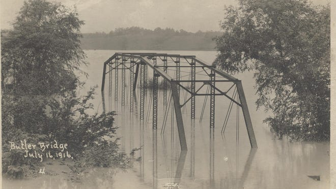 When two hurricanes collided over WNC in 1916, devastation followed. Here the Butler Bridge in Asheville is covered by the flooding of the French Broad River in July 1916.