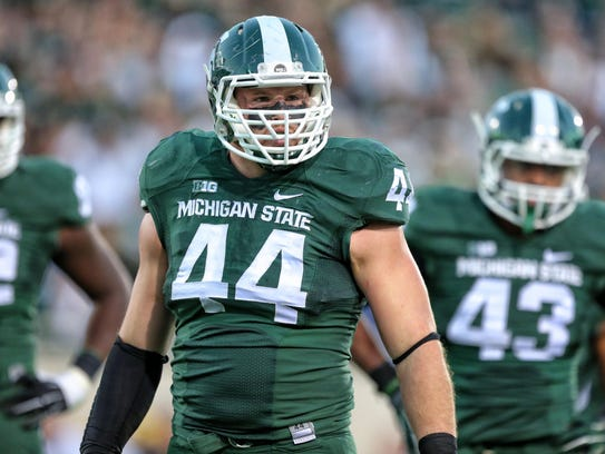 Michigan State defensive end Marcus Rush stands on