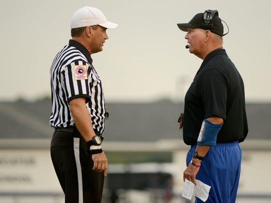 Referee Bob Cannon talks to Stephen Decatur head coach