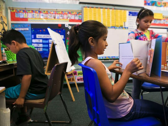 Samantha Fuentes Cano, center, reads during a reading session at Parkwood Elementary School in Clarksville recently. At left is Daniel Patlan and at right is Mardi Regalado Cruz. The Clarksville elementary school has more than 50 percent of its students that are hispanic.