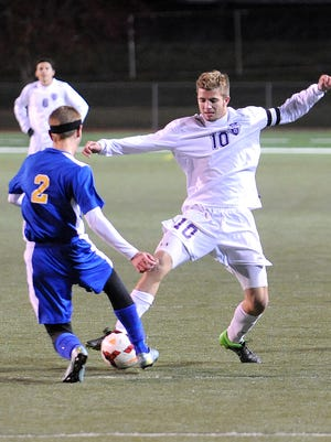 Lexington's Connor Baughman and Ontario's Simeon Malaga battle for control of the ball Thursday night during their Division II boys soccer district championship at Ashland.