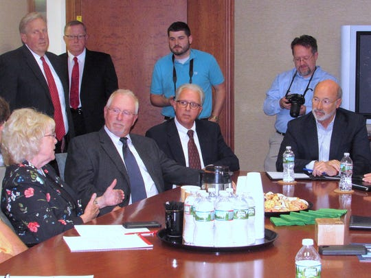 Pennsylvania Gov. Tom Wolf, seated right, listens as