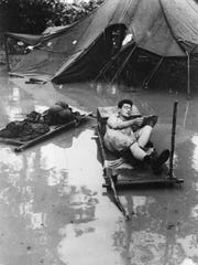 A soldier reads a pocket-sized paperback known as an Armed Services Edition (ASE) in monsoon conditions.