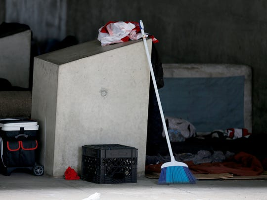 A broom along with tents line the area at the homeless camp under the overpass near the intersection of Third Street and Plum Street.