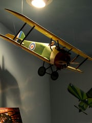 A biplane hangs from the ceiling Oct. 6, 2009, of Andrew Nickless' airplane-themed bedroom in Holt, Mich.