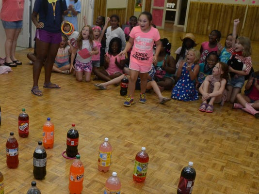 ANI YWCA Camp Jade Bowers tosses a ring over a Coca-Cola bottle on her first try at playing ring toss during the Country Western Carnival held Friday, June 19, 2015 at the YWCA on St. James Street in Alexandria.-Melinda Martinez/The Town Talk