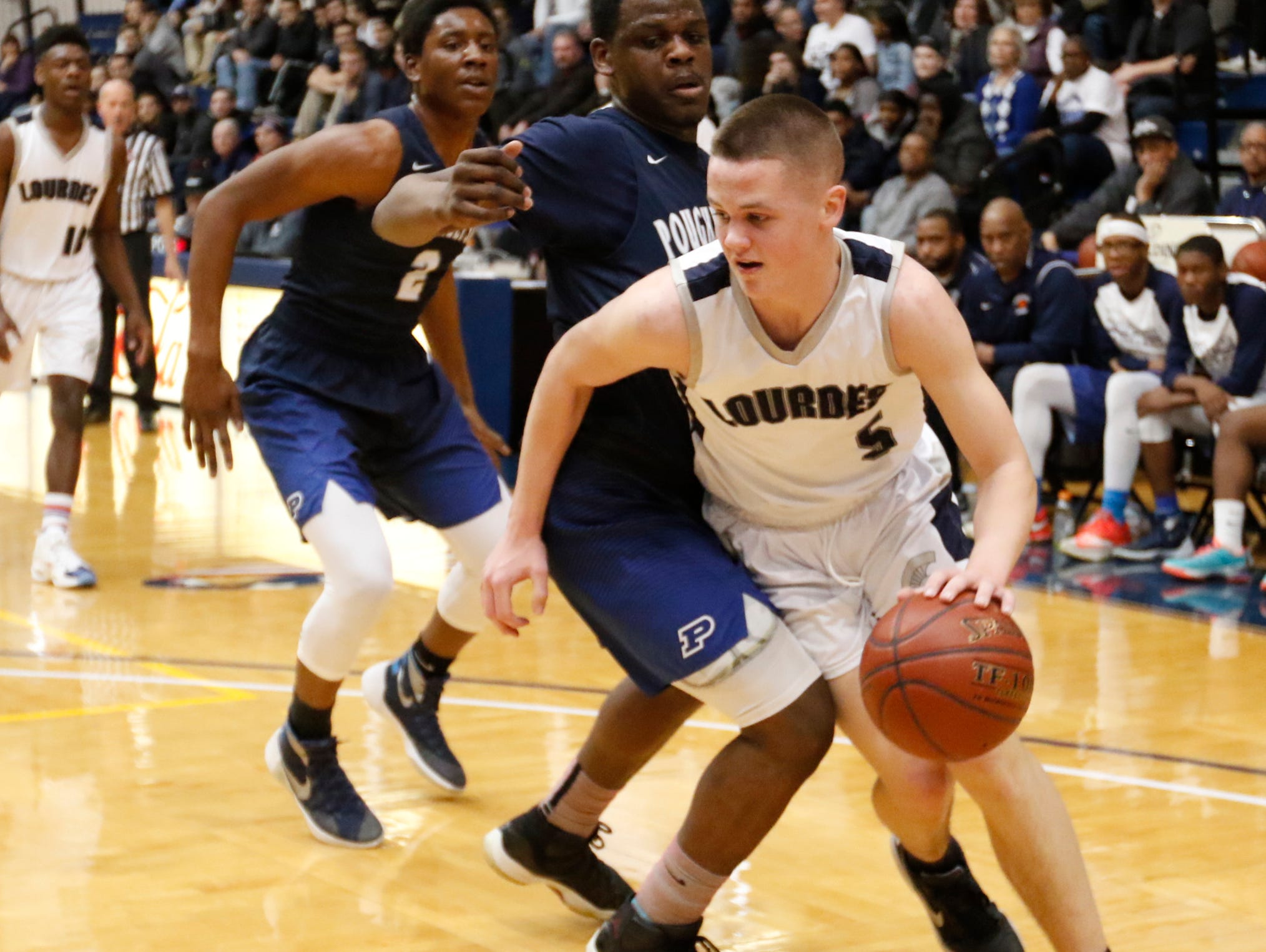 Our Lady of Lourdes High School's Aidan Hildebrand drives past a Poughkeepsie defender during Saturday's victory in the Class A regional finals at Pace University in Pleasantville.