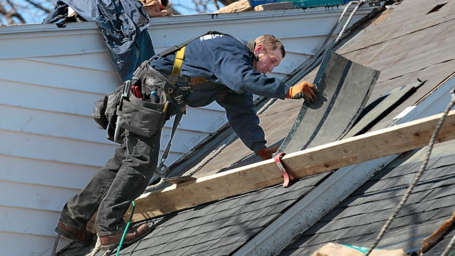 Nicholas Weber, working for Graves Brothers Home Improvement Company of Rochester, reaches for another line of shingles as he works with a crew to reroof a home at 504 Hickory St. in East Rochester on Tuesday.