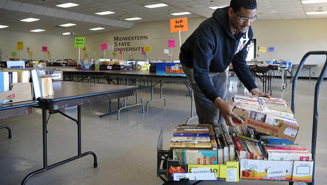 Derek Wherry, a volunteer, organizes stacks of books in preparation for the 17th Annual Wichita Falls Adult Literacy Council Book Sale at the Sikes Lake Center of Midwestern State University. More than 50,000 books will be for sale at one dollar for paperbacks and two dollars for hardbacks. The event runs Friday and Saturday from 9 a.m. tp 8 p.m. with a sneak peek preview Thursday night for $10.