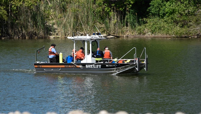 The St. Clair County Sheriff dive team returns from the Black River Wednesday, June 6, 2018, after searching the river for two missing people.