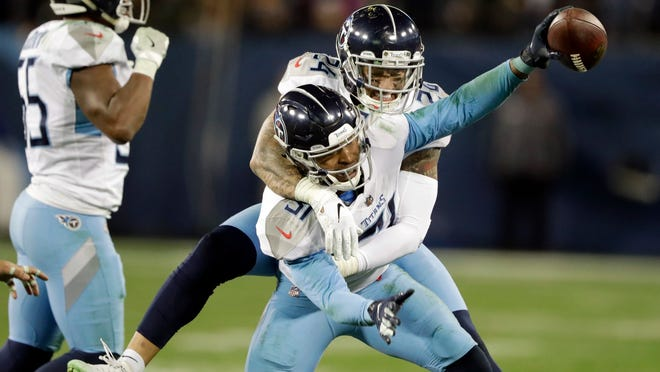 Tennessee Titans free safety Kevin Byard (31) celebrating with Kenny Vaccaro (24) after Byard intercepted a pass against the Washington late in the fourth quarter of an NFL football game in Nashville, Tenn. (AP Photo/James Kenney)