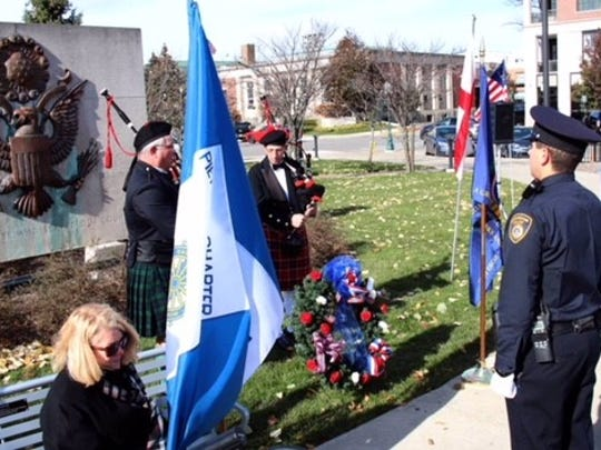Placing wreaths at the World War II monument is DAR Piety Hill President Jan Stafford with Birmingham Police Officers Dave Buttigieg and Alex Linke, who served as members of the Color Guard.