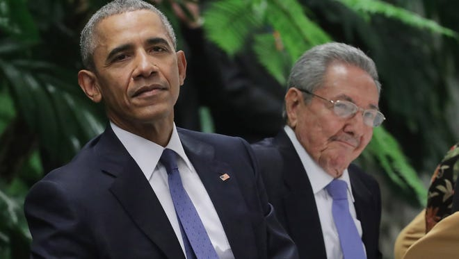 President Barack Obama and Cuban President Raul Castro listen to live music during a state dinner at the Palace of the Revolution on Monday, March 21.