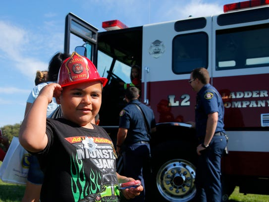 Jason Martinez, 4, tries on his new fire hat during