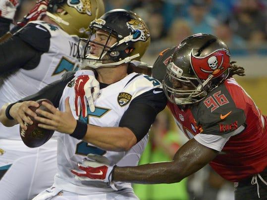 Jacksonville Jaguars quarterback Blake Bortles, left, is sacked by Tampa Bay Buccaneers defensive end Steven Means (96) during the first half of an NFL preseason football game in Jacksonville, Fla., Friday, Aug. 8, 2014. (AP Photo/Phelan M. Ebenhack)
