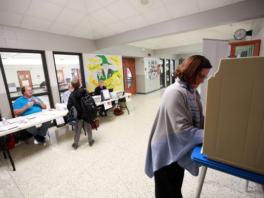Christine Douglas casts her ballot as her 10-year-old