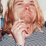 This Dec. 13, 1993 file photo shows Kurt Cobain of the Seattle band Nirvana performing in Seattle, Wash. It's been two decades since the Nirvana frontman took his own life yet he remains on in the thoughts of those he influenced and entertained. He's a touchstone for young musicians clutching guitars the world over and his story is a tale of both inspiration and caution. His influence still ripples across the surface of pop music and his shadow even looms in the hip-hop world where he's been referenced by Jay Z, Kanye, Kendrick Lamar, Drake and Jay Electronica in various ways recently. (AP Photo/Robert Sorbo, file)