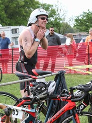 Christopher Hagen straps on his bike helmet as he prepares to transition to the next leg of last year's Apple Duathlon in Sartell.